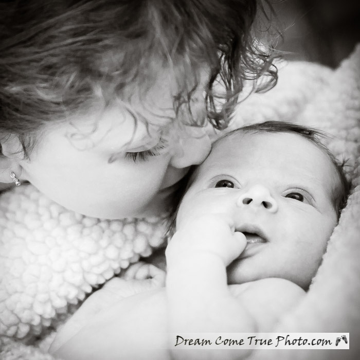 Dream Come True Photo.  Capturing connection: big sister admiring her adorable newborn baby brother.