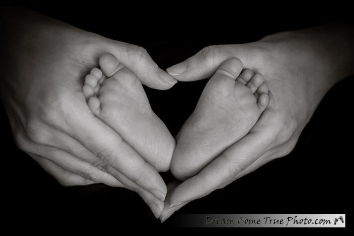 Dream Come True Photo.  Newborn baby feet in mom's hands, shaped like a heart.